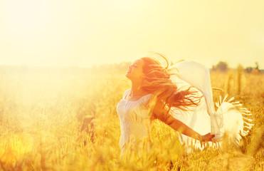 Teenage model girl in white dress running on the spring field