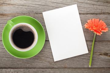 Coffee cup, blank paper and gerbera flower