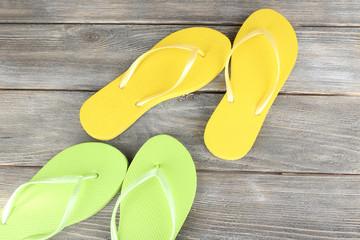 Colorful flip-flops on wooden background