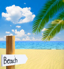 Paradise beach and sea with wooden board showing direction to th