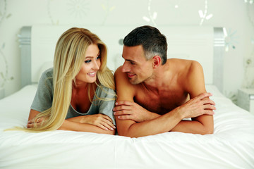 cheerful couple lying on bed at home
