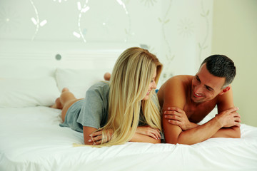 Happy couple lying on the bed and looking at each other