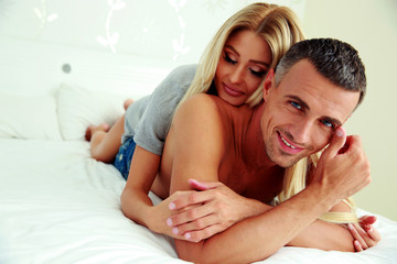Happy couple relaxing on the bed