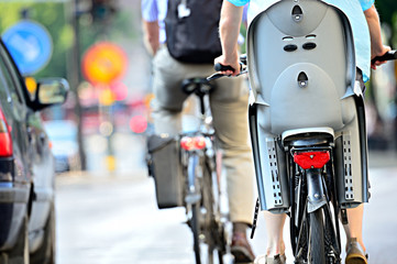 Fototapete - Rear view of bicyclist with child chair