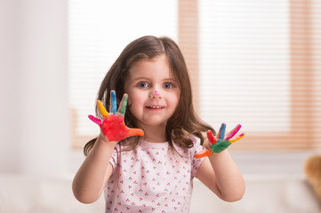 nice little girl with hands in paint.