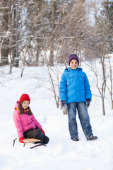 boy and girl playing outside on snow.