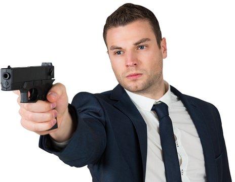 Serious businessman pointing a gun