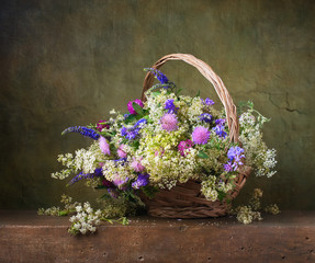 Still life with wild flowers in a basket