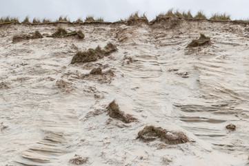 Side of a sand dune eroded by wind and water in a beach in UK