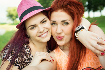 Two cute young women taking a selfie in park in summer