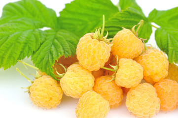 Fresh yellow raspberries with leafs on white background