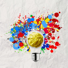splash colors lightbulb crumpled paper background as concept