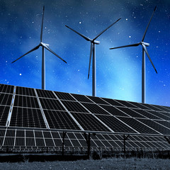 solar energy panels and wind turbines in night.