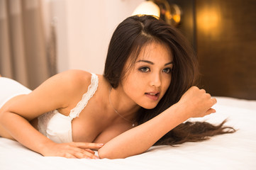 Asian young girl lay down her body on the bed in hotel room