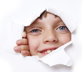 little girl looking out of a hole in a paper