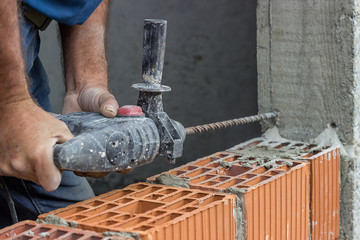Construction worker uses drill to make holes in concrete for for