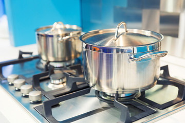 Stove with saucepan on the white modern kitchen