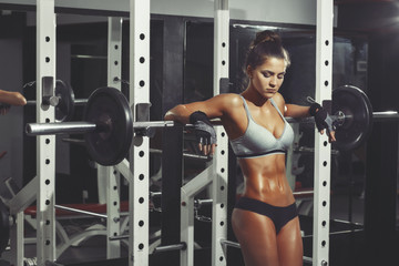 Wall Mural - Woman resting after lifting barbell in gym