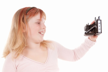 Mädchen macht ein Selfie mit analoger Kamera