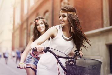Boho girls riding a bike in city