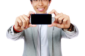 Happy asian man making photo on smartphone. Focus on smartphone
