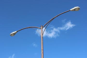 Streetlight against bright blue sky