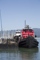 colorful red tugboat docked at a wood pier