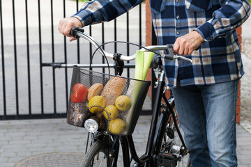 Man and bicycle basket full of groceries