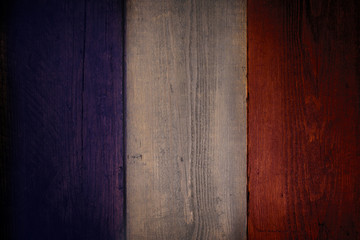French flag over a grunge wooden background.