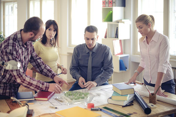 Group of Architects Sitting Around Table Having Meeting