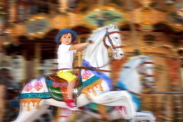 Cute kid, riding on a carousel