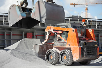 Crane loading cargo ship with gravel
