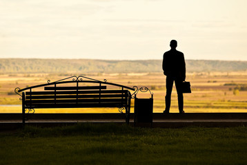 Silhouette of a man with a briefcase near the benches