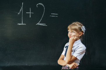 happy school girl on math classes finding solution and solving p