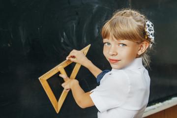Portrait of smart schoolchild standing at blackboard and looking