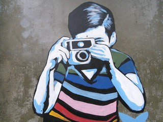 Graffiti art of boy taking photo.