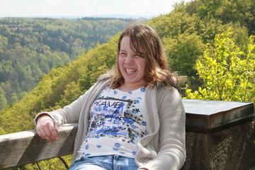 Mädchen lacht vergnügt an Aussichtspunkt im Wald
