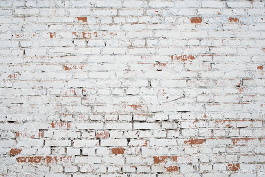 Cracked white grunge brick wall textured background stained old