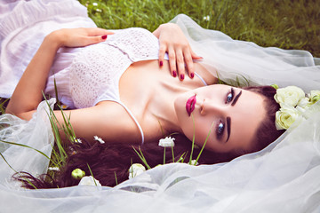 Bride with flowers in hair and veil lying on meadow