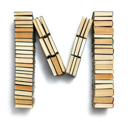 Letter M formed from the page ends of books