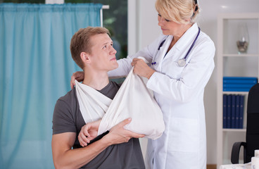 Physician binding a sling
