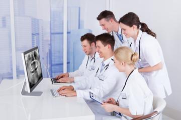 Dentists Examining Jaw Xray On Computer