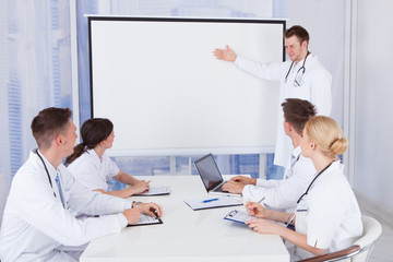 Male Doctor Giving Presentation To Colleagues In Hospital