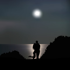 Loving couple on the seashore at night
