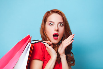 Surprised redhead girl with shopping bags on blue background.