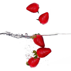 Fresh Strawberries Falling in Water Isolated on White Background