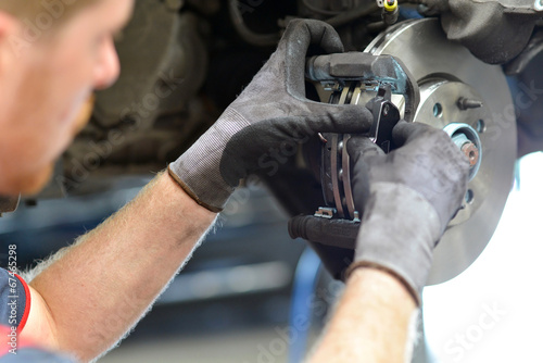 KFZ Mechaniker repariert Bremsen am Auto