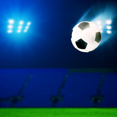 Flying soccer ball over green field, abstract sport backgrounds