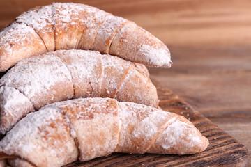 Tasty bagels with sugar powder, on wooden background