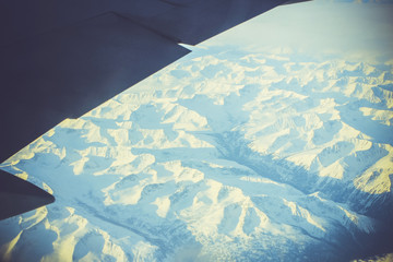 Wing of the plane on blue sky background and snowy mountains,